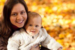 maman et son bébé avec des feuilles mortes en arrière plan
